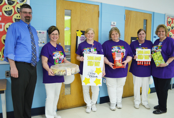 Food service workers in the middle school and Principal James Lupini pose for a picture with thank-you cards and gifts from Lunch Hero Day.